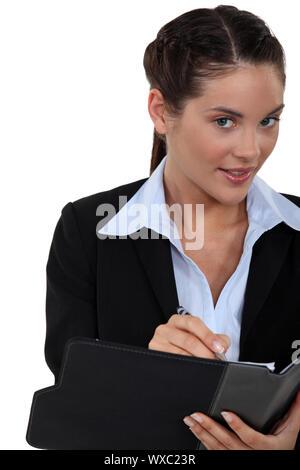 Geschäftsfrau, die ihre Tagesordnung schriftlich - Stockfoto