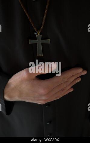 Priester Hand unten Kruzifix auf schwarze Robe Stockfoto