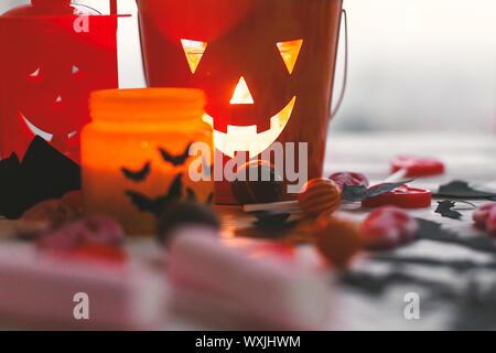Halloween jack o lantern Schaufel, leuchtende Kerze, festliche Candy, Schädel, schwarz Fledermäuse, Geist, Spinne, Dekorationen auf weißem Holz- Hintergrund. Kopieren Sie Platz. - Stockfoto