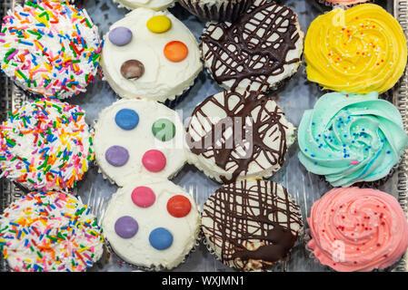 Blick von oben auf die frischen bunten Cupcakes - Stockfoto