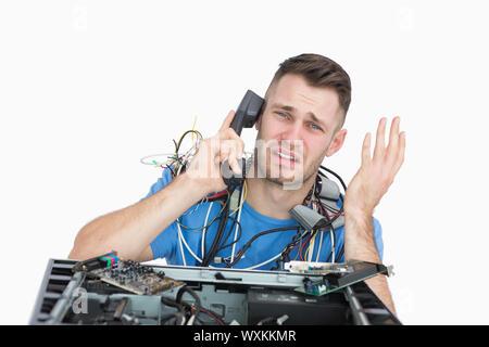 Porträt des jungen frustriert Computer-Ingenieur auf Abruf vor der offenen cpu auf weißem Hintergrund - Stockfoto