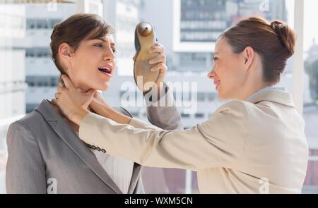 Geschäftsfrau, die sich von ihrer Kollegin erwürgt sie in einem hellen Büro zu verteidigen - Stockfoto