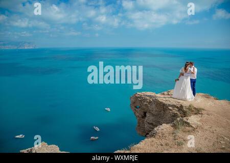 Schönen lächelnden jungen Braut und Bräutigam zu Fuß am Strand, Küssen und Spaß haben, Trauung in der Nähe der Felsen und das Meer. Hochzeit auf Coa - Stockfoto