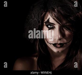 Furchterregende Hexe Porträt isoliert auf schwarzem Hintergrund, attraktive Frau mit unheimlich Make-up, Halloween-Party, Horror-Konzept - Stockfoto