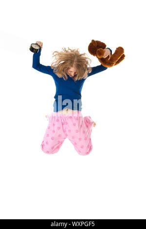 Junge Frau springt in blau und rosa Schlafanzug - Stockfoto