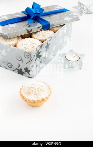Mince Pies in cookie Zinn und auf weißem Hintergrund mit Teelicht und Weihnachten Dekoration. - Stockfoto