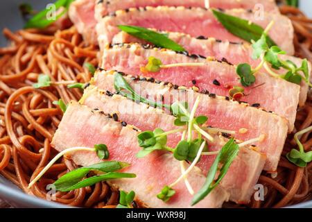 Japanische Soba-Nudeln Buchweizen mit in Scheiben geschnittenen Thunfisch mit Sesam auf dunklen Holztisch - Stockfoto