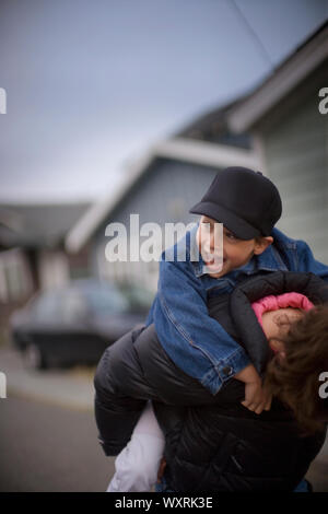 Junge Junge, ein piggyback Ride von seiner älteren Schwester. - Stockfoto