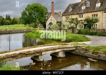 Gelbe Cotswold Kalkstein Fußgängerbrücke über den Fluss Auge im Lower Slaughter Dorf in Cheltenham England mit der Alten Mühle museum Gebäude - Stockfoto