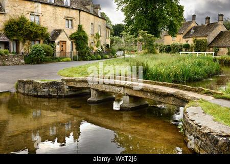 Gelbe Cotswold Kalkstein Fußgängerbrücke über den Fluss Auge im Lower Slaughter Dorf in Cheltenham England - Stockfoto