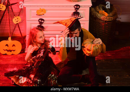 Assistenten und kleine Hexe in Hüte halten Kürbis. Mädchen und bärtiger Mann mit lachenden Gesichtern auf rotem spooky Karneval zimmer Hintergrund. Halloween Party Konzept. - Stockfoto