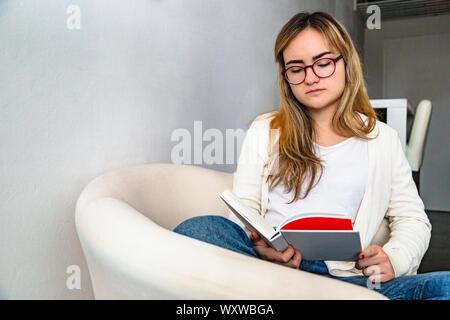 Junge schöne Mädchen bequem im Sessel sitzen und lesen Buch - Stockfoto