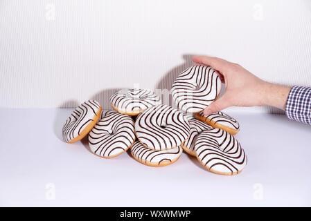Gestreifte Donuts auf einem weißen Hintergrund. - Stockfoto