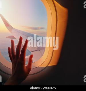 Woman's Hand berühren ein Fenster Glas auf der Ebene im schönen Abendlicht - Stockfoto