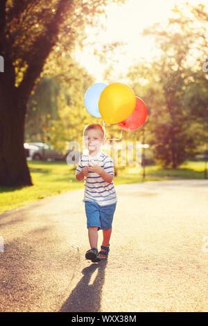 Cute adorable kleine Kaukasischen jungen Kleinkind Kind mit bunten Luftballons im Park Outdoor. Kid genießen zu spielen. Happy birthday Urlaub Feier. - Stockfoto