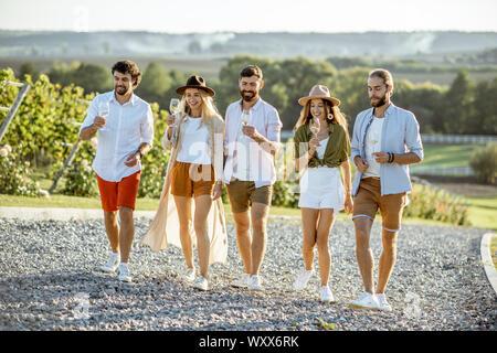 Gruppe junger Freunde gekleidet beiläufig heraus zusammen hängen, Wandern mit Weingläsern auf dem Weinberg an einem sonnigen Tag - Stockfoto