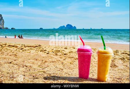 An der malerischen Ao Nang Beach mit Glas erfrischenden tropischen Obst Smoothie von passionsfrucht oder Drachenfrucht Entspannen; frischen lokalen Bars bieten verschiedene Säfte - Stockfoto