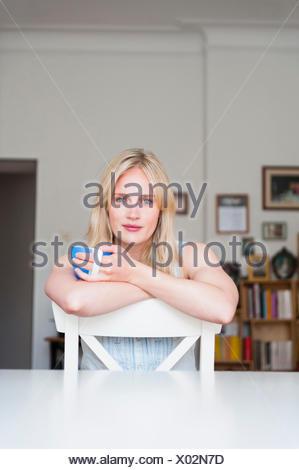 Porträt der jungen Frau Kaffeetrinken auf Stuhl - Stockfoto