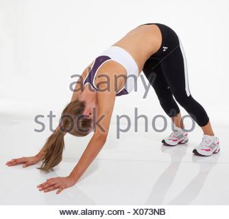 Oberkörper Übung weibliche blondes Haar gebunden zu Pferdeschwanz tragen eine kurze Weste, schwarze Leggings und Trainer, bücken - Stockfoto