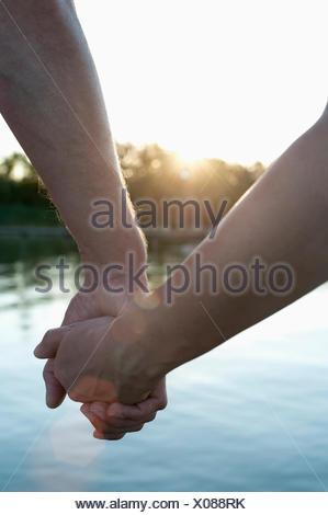 Nahaufnahme des Paares in der Liebe Hand in Hand bei Sonnenuntergang, Bayern, Deutschland