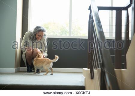 Reife Frau streicheln ihren Hund im Treppenhaus - Stockfoto