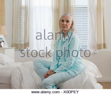Porträt der traurige senior Frau sitzt auf Bett tragen Schlafanzüge