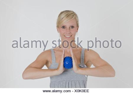 Junge Frau hält einen blauen Spitzen Massage Ball zwischen beide Hände - Stockfoto