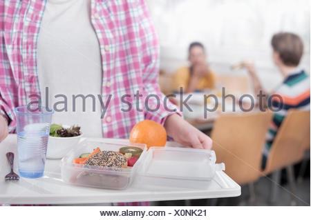 Mittelteil eines Studenten mit Mittagessen in Kantine, Bayern, Deutschland