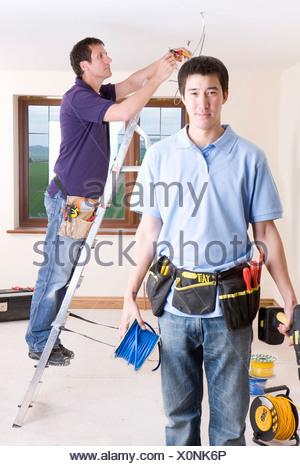 Elektriker hält Kabel Spule und Bohren Sie mit Kollege Verdrahtung ...