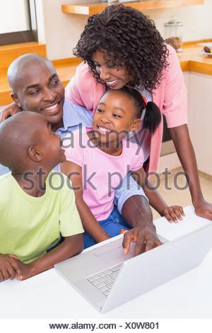 Glückliche Familie mit dem Laptop zusammen