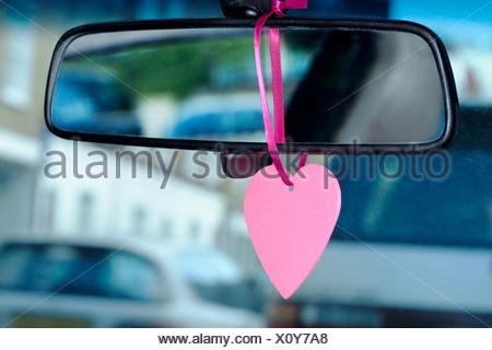 Ein Schmuckstück an einem Rückspiegel hängen - Stockfoto