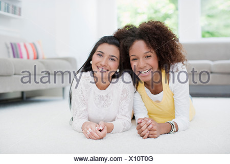 Lächelnde Mädchen im Teenageralter Wohnzimmerboden Handauflegen - Stockfoto