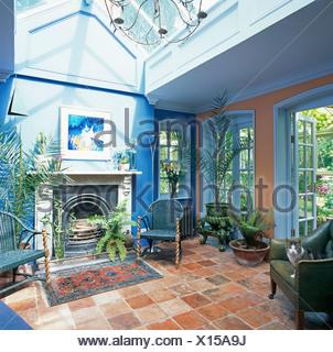 Terrakotta geflieste Boden im Wintergarten Wohnzimmer mit Korbstuhl ...
