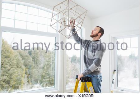 Junger Mann Installation Deckenleuchte Stockfoto, Bild: 84825168 - Alamy