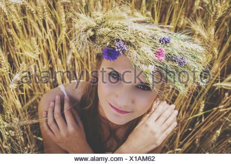 Porträt von schöne junge Frau mit Blumen auf Kopf am Feld Stockfoto