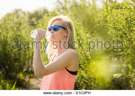 Junge Frau im Park, die Flasche Wasser trinken