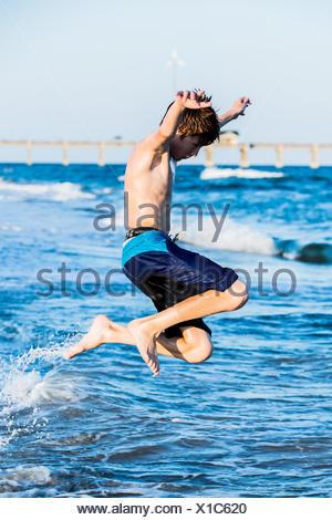 Rothaarige junge am Strand in die Brandung springen - Stockfoto