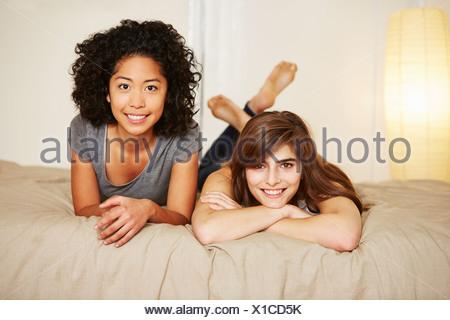 Porträt des jungen Freundinnen auf Bett liegend - Stockfoto