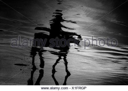 Reflexion der Person auf das Reiten am Strand - Stockfoto