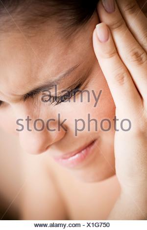 Frau mit Zahnschmerzen oder Kopfschmerzen, hielt ihre Hand zu ihrem Tempel - Stockfoto