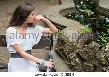 Junge Frau sitzt auf der Bank in der Nähe von Teich Stockfoto