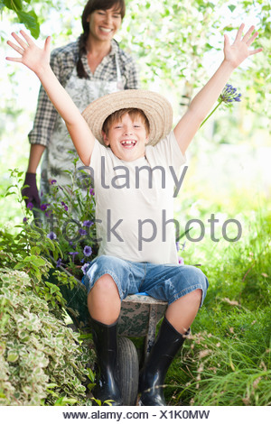 Junge sitzt in Schubkarre von Pflanzen - Stockfoto