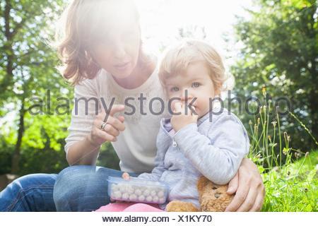 Mutter und weiblichen Kleinkind Süßigkeiten essen im park - Stockfoto