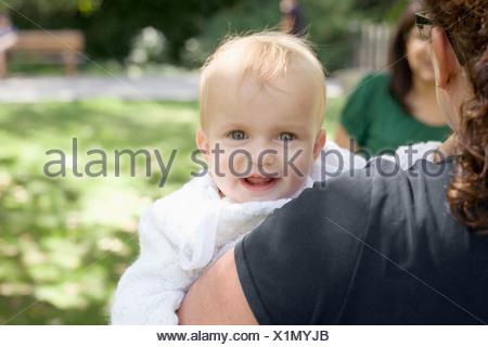 Eine Mutter trägt ihr Babymädchen über die Schulter-Blick - Stockfoto