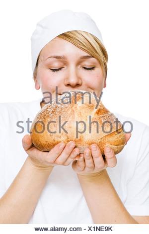 Frau riecht frischer Brotlaib - Stockfoto