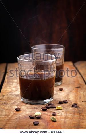 Kaffee im Glas und Zutaten auf Holz Hintergrund Stockfoto