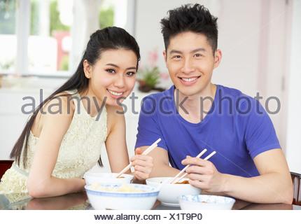 junge frau mit essst bchen zu hause einen asiatischen reisgericht aus einer sch ssel essen. Black Bedroom Furniture Sets. Home Design Ideas