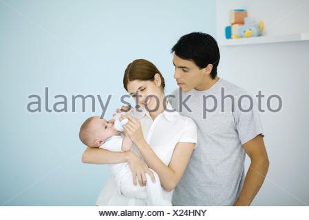 Mutter Fütterung Baby mit einer Flasche, Mann über die Schulter schauen - Stockfoto