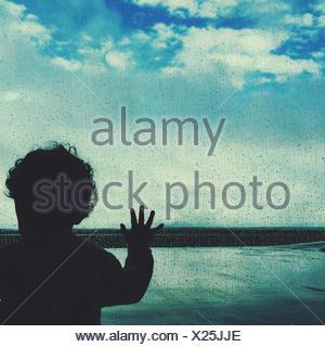 Silhouette eines jungen aus einem Flughafen Fenster - Stockfoto