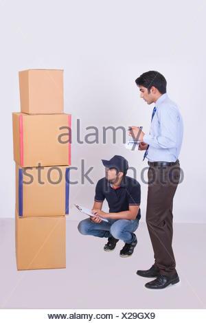 Voller Länge der Lieferbote und Geschäftsmann zählen Kartons auf grauem Hintergrund - Stockfoto
